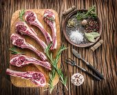 stock photo of lamb chops  - Raw lamb chops with garlic and herbs on old wooden table - JPG