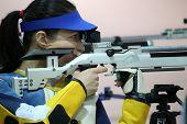image of rifle  - beautiful young woman aiming a pneumatic air rifle - JPG