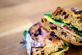 foto of deli  - A deli sandwich on rustic bread on a wood table  - JPG