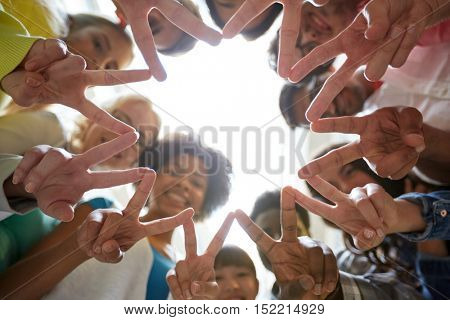 education, friendship, gesture, victory and people concept - group of happy international students o
