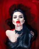 Постер, плакат: Beauty Halloween Sexy Vampire Woman with dripping blood on her mouth lying in a bath full of blood