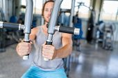 Gym machine closeup on male hands. Male athlete training chest muscles on fitness equipment pec deck poster