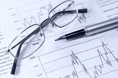 Financial chart pen and glasses.