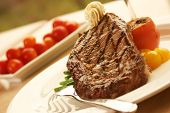 picture of rib eye steak  - 12oz rib eye steak topped with truffle butter and grilled tomato - JPG