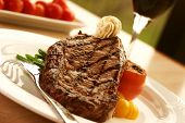 image of ribeye steak  - 12oz ribeye steak topped with truffle butter and grilled tomato - JPG