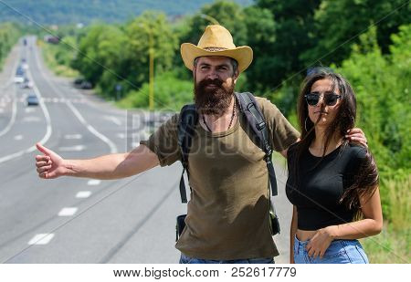 poster of Couple Travelers Man And Girl Hitchhiking At Edge Road Nature Background. Travellers Try To Stop Car