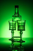 Bottle Of Absinthe With Lead Glasses On Mirror Surface And Dark Green Background poster