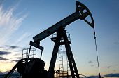 image of oil rig  - Silhouette pump jack on a blue sunset sky background - JPG