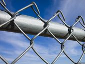 foto of chain link fence  - A brightly lit shot of a chain link fence with blue sky and wispy white clouds in the background - JPG