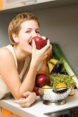 foto of healthy eating girl  - Beautiful girl eating fresh fruits at the kitchen - JPG
