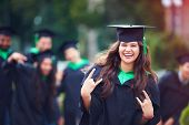 Portrait Of Smiling Successful Indian Student In Graduation Gown With Rock N Roll Hand Gesture poster