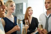 Cheerful girls and guys with champagne discussing something funny while cheering up at party poster