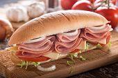 A Delicious Submarine Sandwich With Deli Meats, Lettuce, Tomato, Onion And Cheese On A Sub Bun. poster