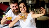 Couple In Love On Date Drinks Beer. Couple Cheerful Mood Drinking Beer In Pub. Man Bearded Hipster A poster