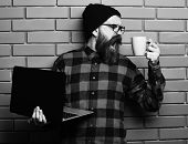 Hipster Holding Laptop With Mag Or Cup In Red Black Checkered Shirt With Hat And Glasses On Brown Br poster