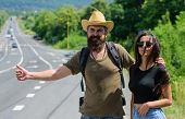 Couple Travelers Man And Girl Hitchhiking At Edge Road Nature Background. Travellers Try To Stop Car poster