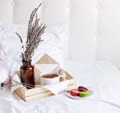 Morning Breakfast In Bed Wooden Tray With A Cup Of Tea, Sweet Colorful French Macaroons, Love Letter poster
