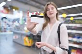 Happy Woman Is In The Supermarket And Shows A Credit Card. Credit Card Is In The Hands Of The Buyer  poster