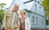 old age, accommodation and real estate concept - happy senior couple holding hands over living house poster