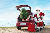 Authentic Santa Claus Near Red Car With Gift Boxes And Christmas Tree On Beach poster