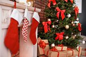 Beautiful Christmas Tree And Gifts Near Decorative Fireplace With Stockings Indoors poster