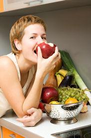 picture of healthy eating girl  - Beautiful girl eating fresh fruits at the kitchen - JPG