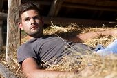 stock photo of bare chested  - Handsome caucasian young man in the hay barn - JPG