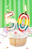 stock photo of 50th  - fiftieth birthday cupcake with white frosting and green decorative background - JPG