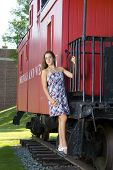 picture of caboose  - Attractive teenage girl in a dress standing on the steps of a red caboose - JPG