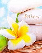 Beautiful spa still life on the beach, spa stones, yellow frangipani flower, tropical resort, summer