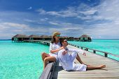stock photo of couple sitting beach  - Couple on a tropical beach jetty at Maldives - JPG