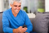 cheerful middle aged man reading emails on smart phone