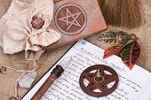 stock photo of wiccan  - wooden pentacle with incense burning with hand written book of shadows and fall leaves  - JPG