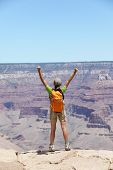 Happy hiker by Grand Canyon south rim cheering happy with arms raised up enjoying the beautiful scen