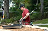image of red siding  - Young man works to put siding on his home - JPG