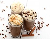 stock photo of cinnamon  - Ice coffee with whipped cream and coffee beans on a white table - JPG