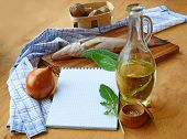 stock photo of clary  - Opened notebook and fish potato olives on cooken table - JPG