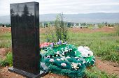 pic of tribute  - black tomb with floral tributes at cemetery - JPG