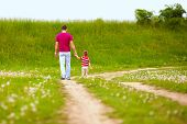 stock photo of walking away  - father and son walking rural footpath - JPG