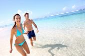 stock photo of woman bikini  - Couple running on a sandy beach - JPG
