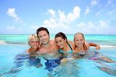 foto of bathing  - Family of four bathing in swimming pool - JPG