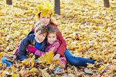 Mother with crown of yellow maple leaves on her head sits embracing her children in drift of fallen