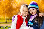 picture of 11 year old  - Close portrait of two happy smiling laughing and hugging girls 11 years old sitting on the bench in autumn park