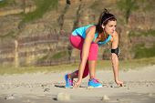 stock photo of sprinters  - Fitness woman with earphones in ready for running starting line position on the beach - JPG