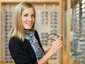 Portrait of beautiful woman holding glasses in optician store