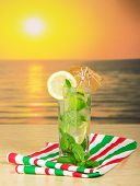 Cold drink with lemon slice agains sea sunset