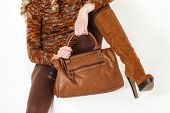 image of leggins  - detail of sitting woman wearing brown clothes and boots with a handbag - JPG