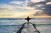 picture of waikiki  - A surfer enjoys the sunset after a surfing session in Waikiki - JPG