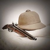 Vintage picture of accessories for safari hunters. Tropical cork helmet and big bore pistol on a ani