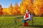 image of 11 year old  - Happy blond 11 years old girl with amazing smile with books textbooks coffee and backpack sitting on the bench in the autumn park on sunny day - JPG